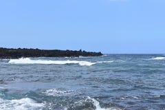 Waves crashing on a black rocky beach stock photo