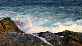 Pacific Ocean Waves on Rocks. Blue Pacific Ocean water, with white foam waves crashing on and flowing over ocean side rocks in the late afternoon. The actual Stock Photos