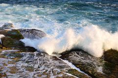 Pacific Ocean Waves on Rocks. Blue Pacific Ocean water, with white foam waves crashing on and flowing over ocean side rocks in the late afternoon. The actual Stock Photography