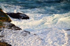 Pacific Ocean Waves on Rocks. Blue Pacific Ocean water, with white foam waves crashing on and flowing over ocean side rocks in the late afternoon. The actual Stock Photo