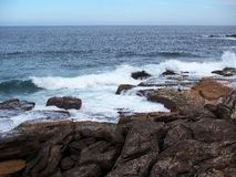 Pacific Ocean Waves on Rocks. At South Bondi Beach, Sydney, Australia, late Summer afternoon Stock Photos