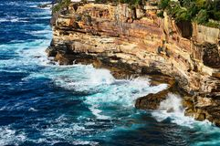Pacific Ocean Waves on Sandstone Cliffs, Australia. Rough Pacific Ocean waves crashing on the bottom of weathered and eroded sandstone cliffs, Vaucluse, Sydney stock photo