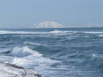 Pacific Ocean, waves and views of the snow-covered hill in winter in sunny weather in Kamchatka, Russia stock photos