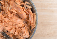 Pacific pink salmon in an bowl on a table. Top close view of Pacific canned pink salmon in an old stoneware bowl atop a wood table Stock Photography