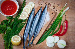 Pacific sauries with vegetables on wood table. Horizontal top view. Royalty Free Stock Images