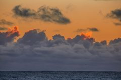Pacific Sunset. The light from the setting sun casts a soft light on clouds over the Pacific Ocean at California`s central coast stock photo
