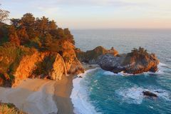 Pacific Sunset at McWay Falls, Julia Pfeiffer Burns State Park, Big Sur, California. Beautiful McWay Falls drops through the cliffs onto a secluded sandy beach royalty free stock images