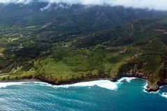 Pacific surf on the coast of the island of Maui in Hawaii. Aerial view of Maui`s eastern coastline shows everything from Pacific surf to mountains and clouds Royalty Free Stock Photos