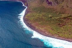 Pacific surf on the coast of the island of Molokai in Hawaii. Aerial view of the curvy coastline, green shore, and pounding surf on the island of Molokai, Hawaii Royalty Free Stock Images