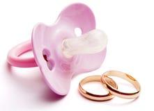 Pacificador del bebé y anillos de bodas, conceptuales Imagen de archivo