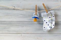 Pacificador y calcetines del bebé que cuelgan en cuerda para tender la ropa en fondo de madera fotos de archivo libres de regalías