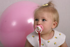 Pacified. Baby girl sucking on a pacifier Stock Image