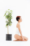 Pacified african american young woman near small tree in pot Royalty Free Stock Images