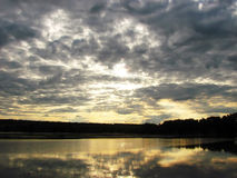 The pacified evening landscape of the sky and lake. Beams of the setting sun through clouds are reflected in quiet water Stock Photo