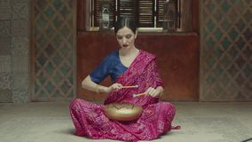 Pacified woman playing glucophone with drums. Attractive female performing traditional indian music using hank drum with signed om symbol while sitting on floor stock video footage
