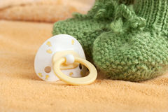 Pacifier and the baby booty on a blanket Stock Image