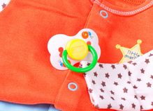 Pacifier and baby clothes Royalty Free Stock Photos