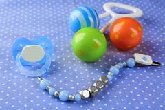 Pacifier clip with place for baby name, dummy and rattle toy. On table Royalty Free Stock Photo