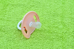 Pacifier on the green towel Stock Photography