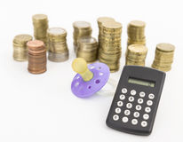 Pacifier with hard money and pocket calculator Royalty Free Stock Image