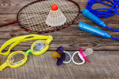 Pacifier and sports equipment: the birdie is on the racket, skipping rope, swimming goggles on wooden background. Stock Photography