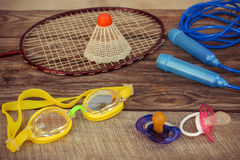 Pacifier and sports equipment: the birdie is on the racket, skipping rope, swimming goggles Royalty Free Stock Images