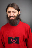 Pacifist - peace and love. Smiling man with black beard with symbol of peace on his sweater Stock Photos