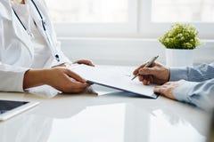 Pacjent podpisuje raport medycznego z jego lekarką zdjęcia stock