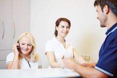 Pacjent sprawdza wewnątrz przy lekarkami recepcyjnymi Zdjęcie Stock