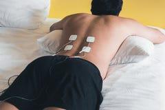 Pacjent stosuje elektryczną pobudzenie terapię na plecy Electri zdjęcie royalty free
