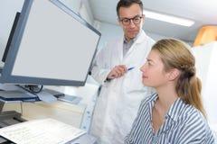 Pacjenta i lekarki spojrzenie przy ekranem tp dyskutuje traktowanie szczegóły zdjęcie royalty free