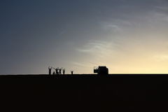 A pack of adventurers salute from the top of a grand sand dune while enjoying a beautiful summer sunset in Dakhla Oasis, Egypt Stock Photos