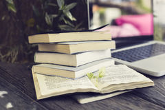 Pack of books with laptop on the wooden table Stock Image
