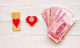 Money concept. pack of chinese currency on white rustic background woth origami heart. Pack of chinese currency on white rustic background. chinese yuan and Royalty Free Stock Photos