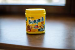 Pack of chocolate and cacao drink Nesquik by Nestle on wood background stock photography