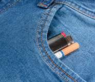 Pack of cigarettes and lighter in pocket jeans Stock Images