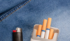 Pack of cigarettes and lighter in pocket jeans Stock Image