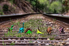 Pack of dinosaurs walking away on railroad tracks Stock Photos