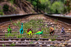 Pack of dinosaurs walking on railroad tracks Stock Photo