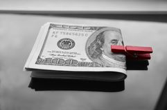 A pack of dollars clamped in a red clothespin. In black and white Royalty Free Stock Photos