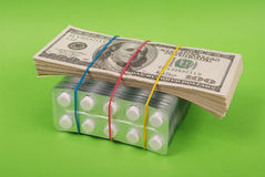Pack of dollars lays on packing of white tablets Stock Photography