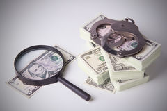 Pack of dollars with magnifier and handcuffs Stock Image
