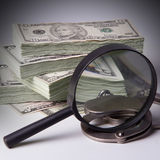 Pack of dollars with magnifier and handcuffs Stock Photo
