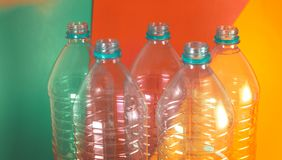 A pack of 5 empty and recyclable water bottles, with no caps, on a colored vibrant background with sea green, orange and stock photos