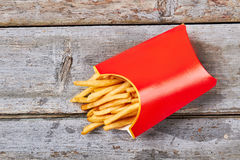 Pack of fries on wood. Fries carton on wooden surface. Control your cholesterol level Royalty Free Stock Photography