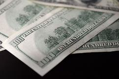 A pack of hundred dollar bills on a dark background. Close up Royalty Free Stock Photos