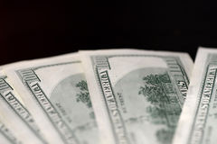 A pack of hundred dollar bills on a dark background. Close up Royalty Free Stock Images
