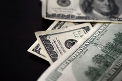 A pack of hundred dollar bills on a dark background. Close up Stock Photos