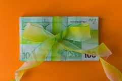 Pack of hundred euro banknotes with green bow-knot on orange desk, gift or dividends concept, european union money. Pack of hundred euro banknotes with green bow stock photos