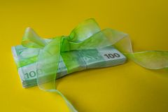 Pack of hundred euro banknotes with green bow-knot on yellow desk, gift or dividends concept, european union money. Pack of hundred euro banknotes with green bow stock photo